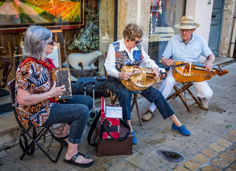 Trio of seated musicians playing Hurdy Gurdys in the street in Beaune, Burgundy, France. On 21 June 2014 stock image