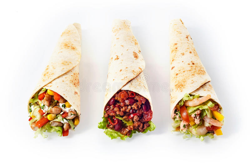 Trio of Tex Mex Fajita Wraps with Various Fillings. High Angle Still Life of Trio of Tex Mex Fajita Wraps Wrapped in Grilled Flour Tortillas and Filled with stock photography