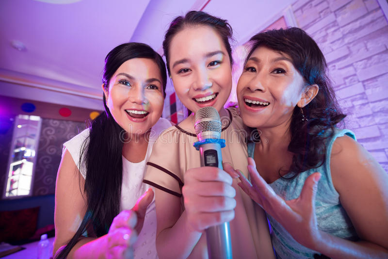 Trio. Three Vietnamese women singing a song in the karaoke bar stock images