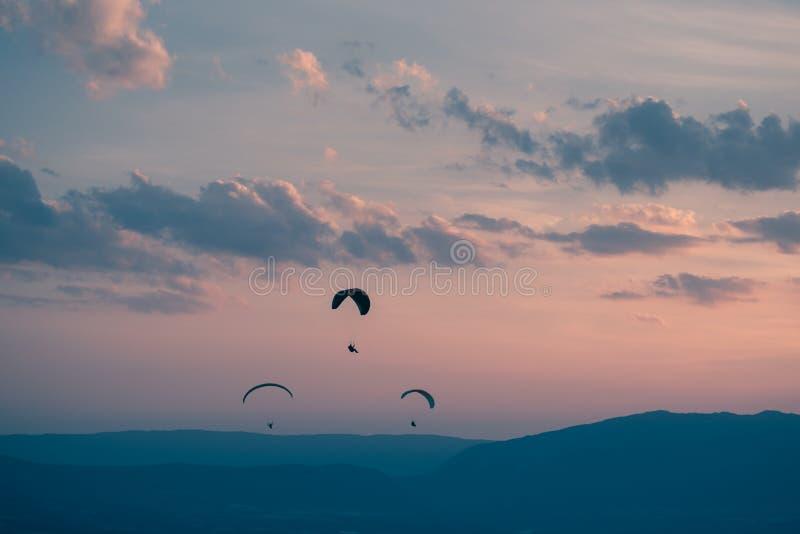 Trio van glijschermen bij zonsondergang over Genève, Zwitserland stock afbeelding