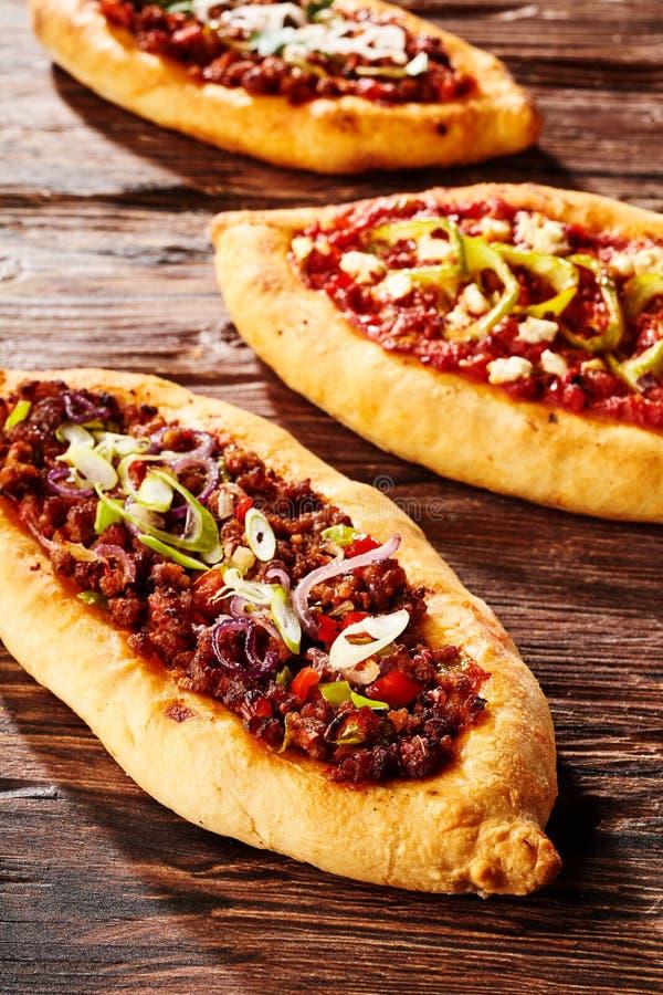 Trio van vers gebakken pizzabroden op lijst stock foto