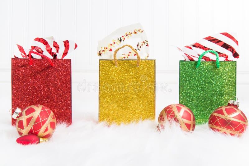 Trio von glittery Geschenktaschen in Folge auf einem weißen Hintergrund und einem Pelz mit Rot und Goldweihnachtsverzierungen lizenzfreie stockfotos