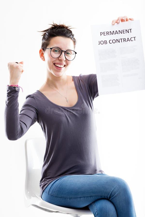 Triomfantelijke vrouw die haar baancontract houden stock foto