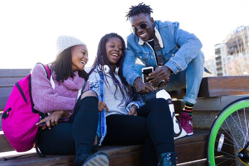 Triovrienden die mobiele telefoon in de straat met behulp van stock afbeelding