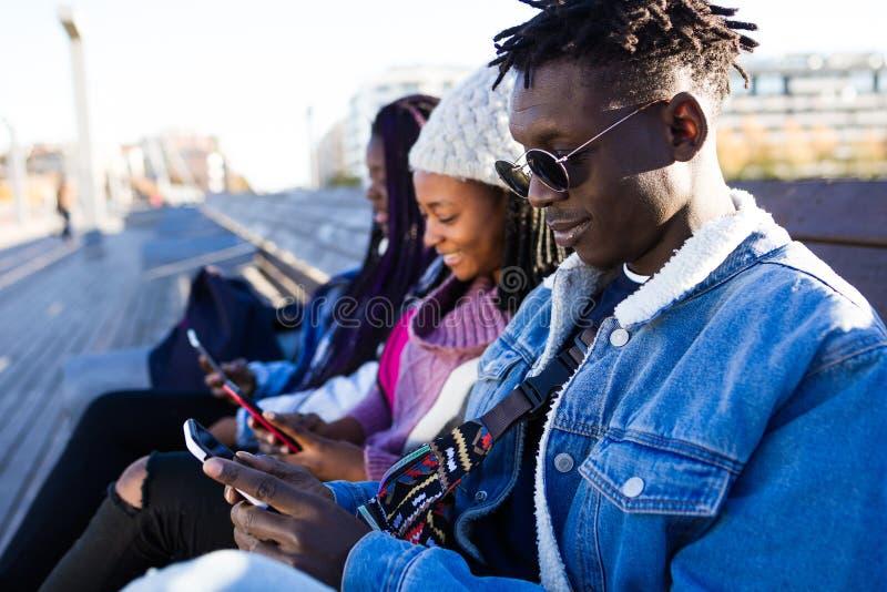 Triovrienden die mobiele telefoon in de straat met behulp van royalty-vrije stock fotografie
