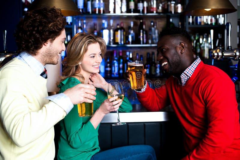 Triovrienden in een bar het drinken bier stock afbeelding