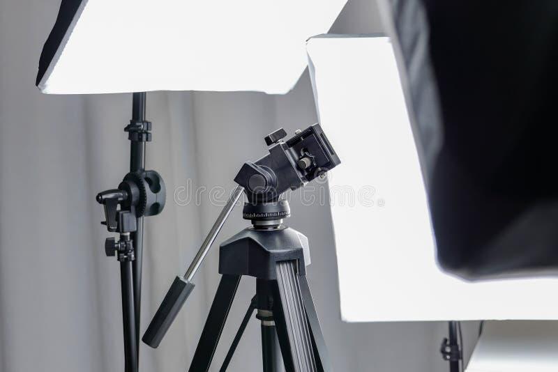 Tripé de câmera em um estúdio da foto com equipamento do relâmpago fotografia de stock royalty free