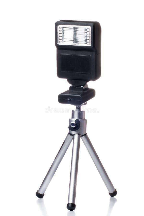 Tripé pequeno com um flash para a câmera isolada sobre imagens de stock