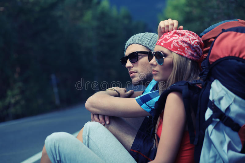 Trip. Two young people tourists hitchhiking along a road royalty free stock photo