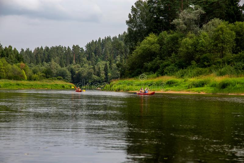 Trip by boat on the river during summer. People boating on river Gauja in Latvia, peacefull nature scene. By boat through the river. Boat trip along the Gauja royalty free stock photos
