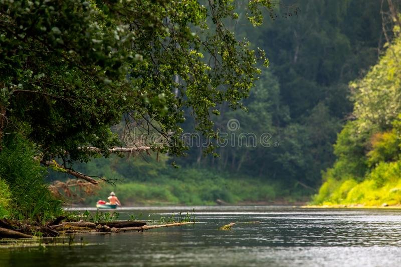 Trip by boat on the river during summer. People boating on river Gauja in Latvia, peacefull nature scene. By boat through the river. Boat trip along the Gauja royalty free stock images