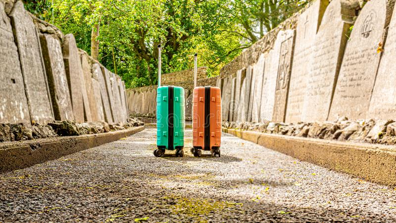 The trip without return, two suitcases on a sidewalk between tombstones in the Abbey Graveyard in the village of Athlone royalty free stock photography