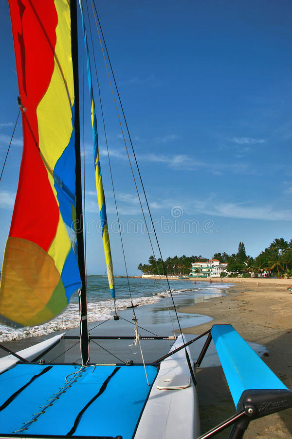 A trip to Paradise by a sailboat catamaran. A catamaran is a multi-hulled watercraft featuring two parallel hulls of equal size. A small sailing catamaran with stock photography