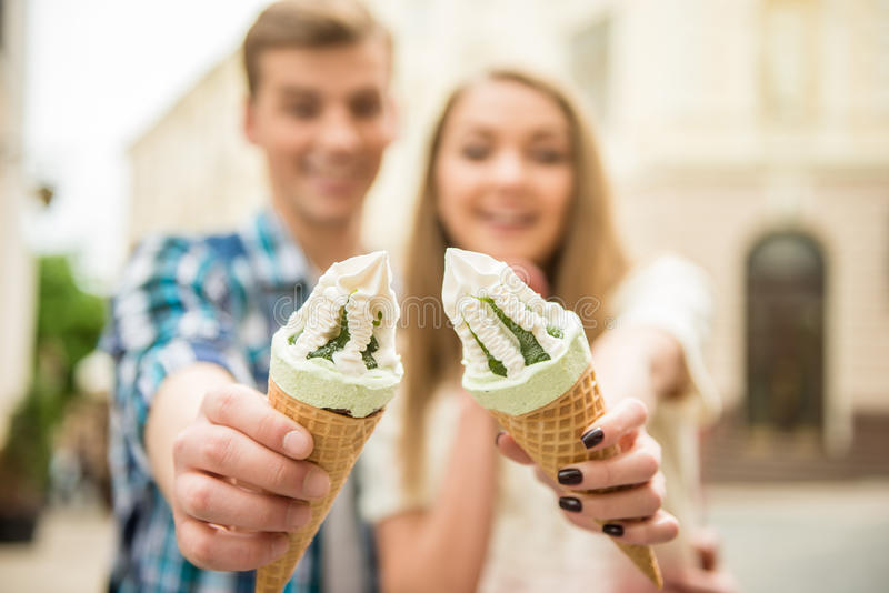 Trip. Young beautiful couple walking in the street and enjoying ice-cream. Romantic date royalty free stock images