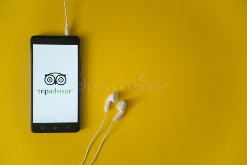 Tripadvisorembleem op het smartphonescherm op gele achtergrond stock afbeeldingen