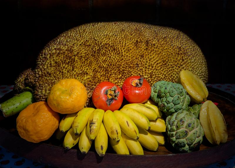 Tripical fruits in wooden bowl stock photography