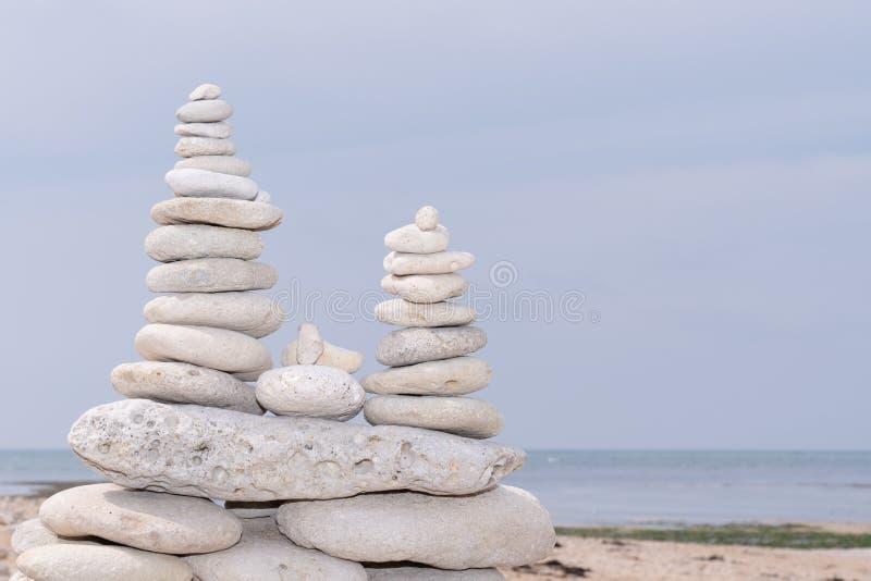 Triple balance tower white grey pebble on a beach royalty free stock image
