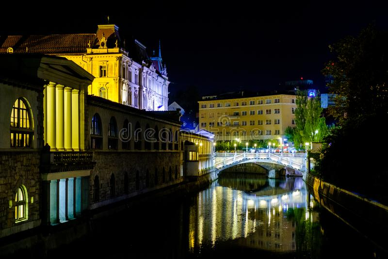 Triple Bridge city centre of Ljubljana and the River Ljubljanica illuminated at night, Slovenia stock photo