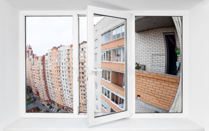 Triple-casement pvc window with view at the facade of multi-apartment houses with balconies. Triple-casement pvc window with view at the facade of multi stock photography