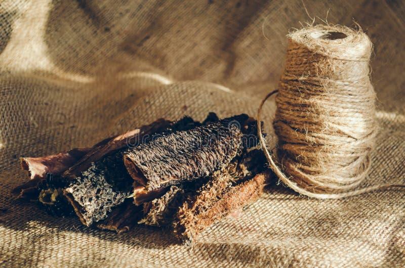 Triple de boeuf sec en baguettes Est tout près une bobine de la ficelle brute à lier Festins pour des chiens Les bâtons se trouve photo libre de droits