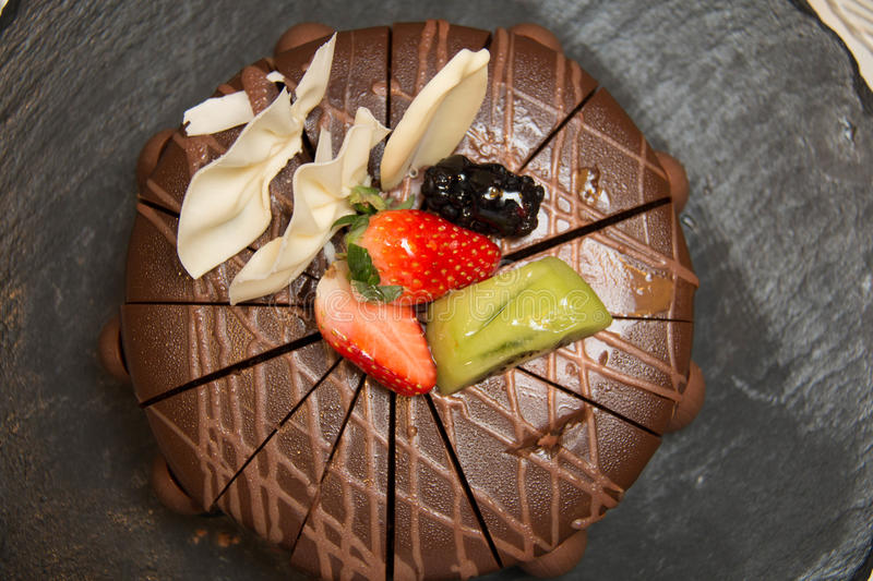 Triple layer chocolate cake. On top with fresh fruit royalty free stock photo