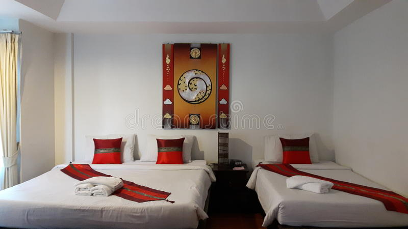 Triple room bed along White Bedding and White Red Pillow with modern art warm tone picture wall on the background royalty free stock images