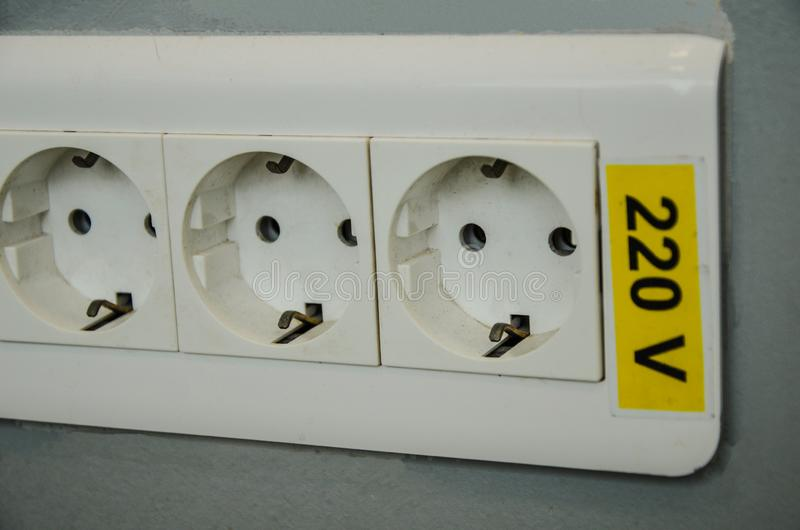 A triple wall jack, 220 v, electric symbol. Close up of a triple white wall jack, 220 v, electric symbol royalty free stock photo