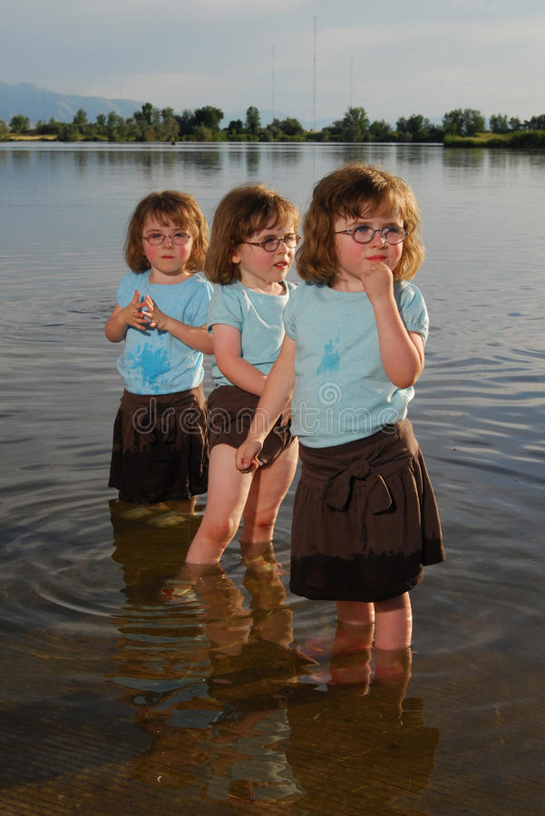 Triplets playing in the lake royalty free stock image