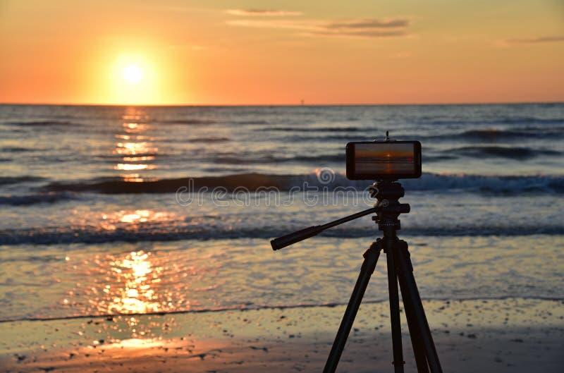 Tripod, inteligentny telefon komórkowy, plaża i zachód słońca obraz stock