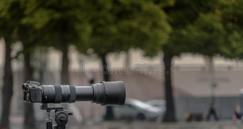 Tripod-mounted 35 mm camera with a large lens of long focal length against a deliberately blurred background royalty free stock photo