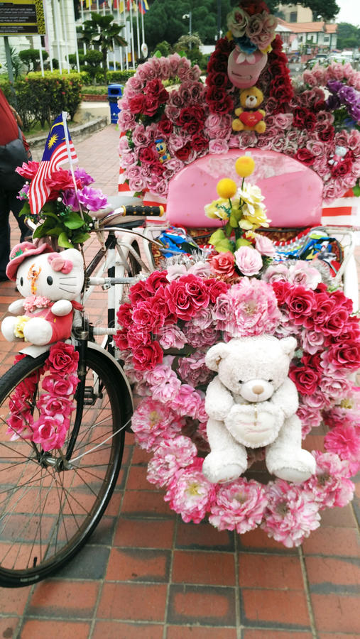 Trishaw decorated with colorful flowers in Malacca, Malaysia stock images