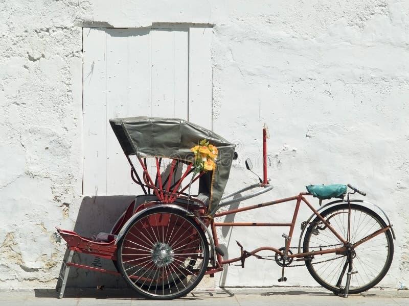 Trishaw die bij een witte muur wordt geparkeerd royalty-vrije stock afbeeldingen