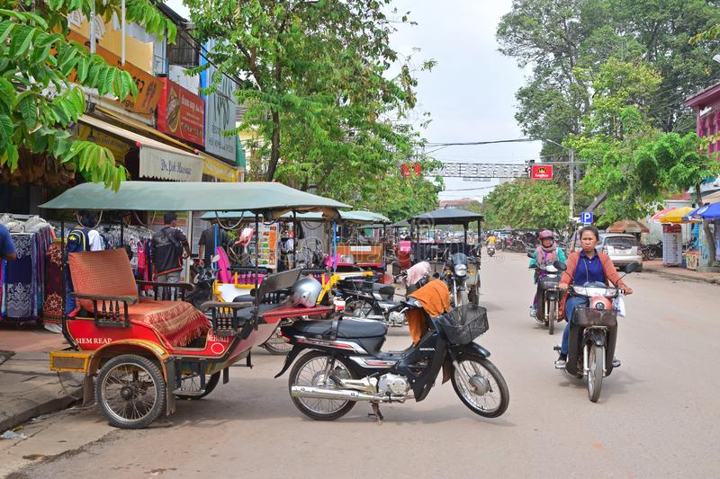 Trishaw parked nearby around the popular Pub Street in the middle of the Cambodian city. This image is taken at the entrance of the busy crowded drinking area stock photography