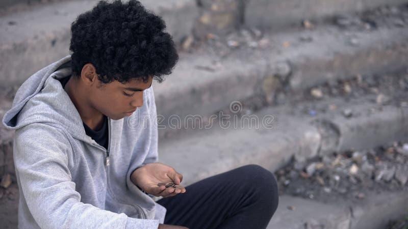 Triste adolescent regardant les pièces de monnaie à la main assis à l'extérieur, chômage urbain images libres de droits