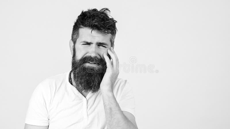 Triste barbu ayant mal aux dents, sur fond blanc Concept Toothache Un jeune homme frustré qui touche sa joue et garde les yeux photo stock