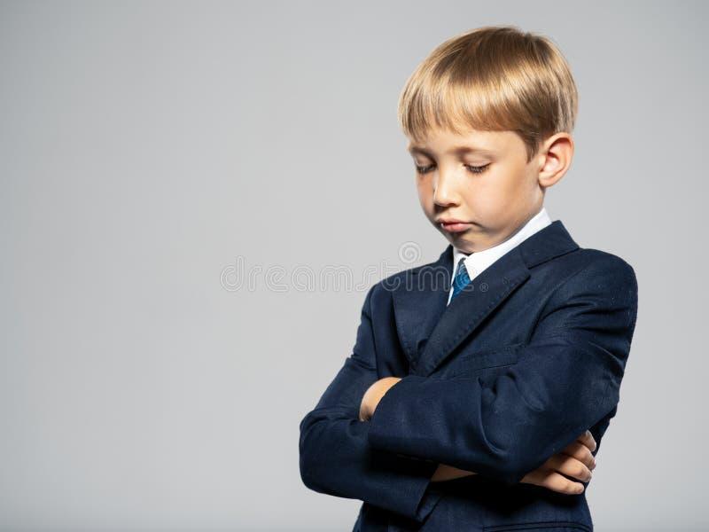 Triste chico rubio vestido con traje formal con corbata azul mirando hacia abajo Un chico disgustado con un traje de negocios azu foto de archivo libre de regalías