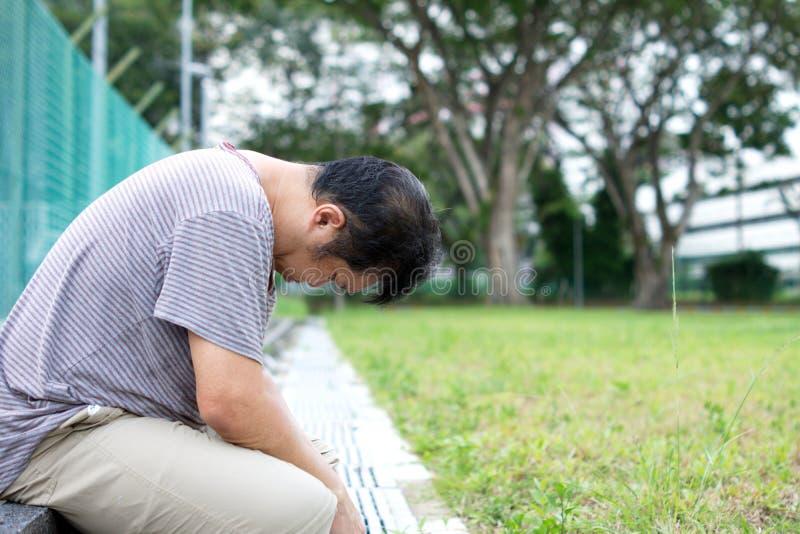 Triste Chinois d'Asie avec la tête assise au sol photographie stock