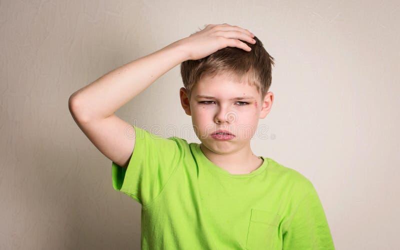 Triste del muchacho del preadolescente ofendido con la contusión y el rasguño en su por de la cara fotografía de archivo