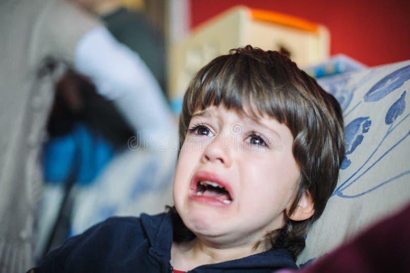 Triste e gridando bambino nella sua casa fotografia stock