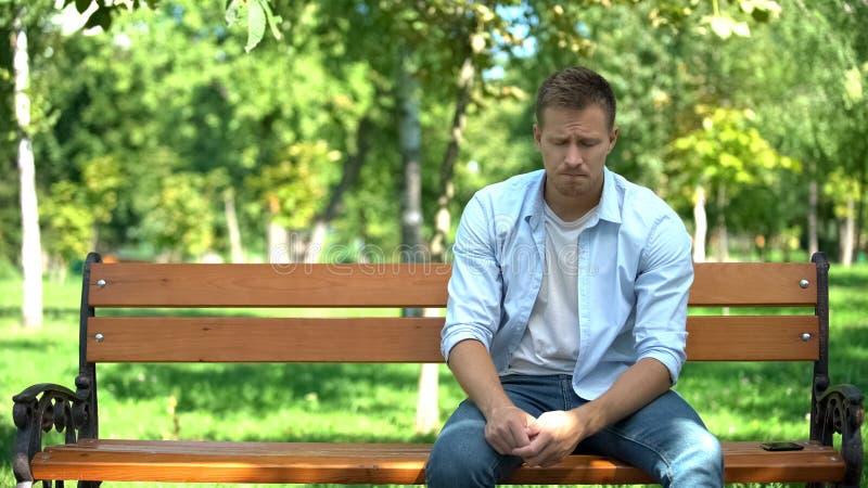 Triste joven sentado solo en el banco del parque, crisis de ruptura, problema de desesperanza foto de archivo