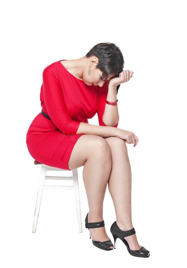 Triste mais a mulher do tamanho que senta-se na cadeira isolada imagens de stock royalty free