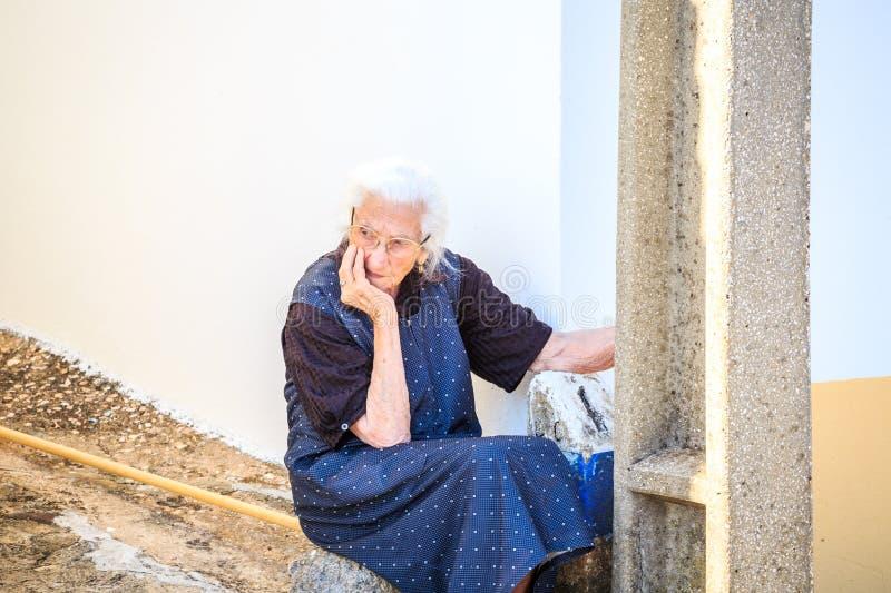 Triste, pensando, seduta worring della donna più anziana all'aperto immagini stock libere da diritti