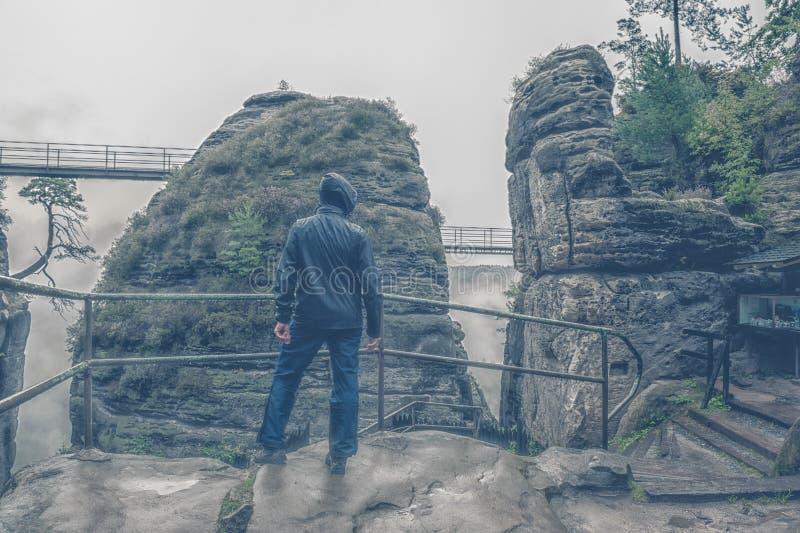 Triste só um homem não identificado está na chuva e na névoa sobre um penhasco Tentativa possível do suicídio fotografia de stock