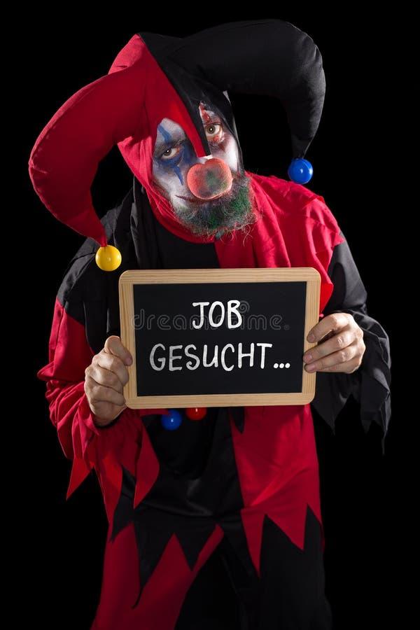Tristement le clown tenant une ardoise avec le travail allemand des textes a voulu, concept photographie stock libre de droits