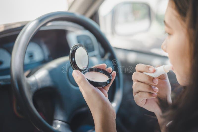 A tristeza, o motorista foi colada no tráfego motorista da mulher que aplica a composição usando o espelho de rearview no carro e foto de stock royalty free