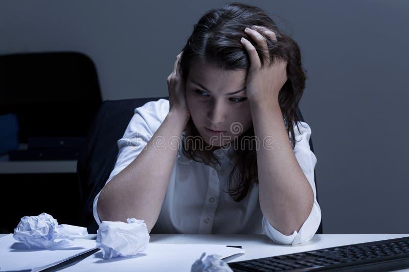 Tristezza durante le ore straordinarie nell'ufficio immagine stock libera da diritti