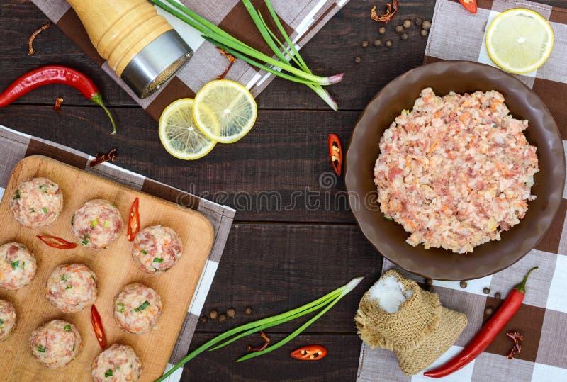 Triti, spezie, le cipolle verdi - gli ingredienti per la preparazione delle polpette su un fondo di legno scuro fotografia stock libera da diritti
