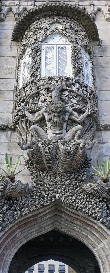 Triton sculpture over the gateway of creation at the Pena Palace. Vertical panoramic view of Triton sculpture supporting a bay window over a gateway at the Pena stock images