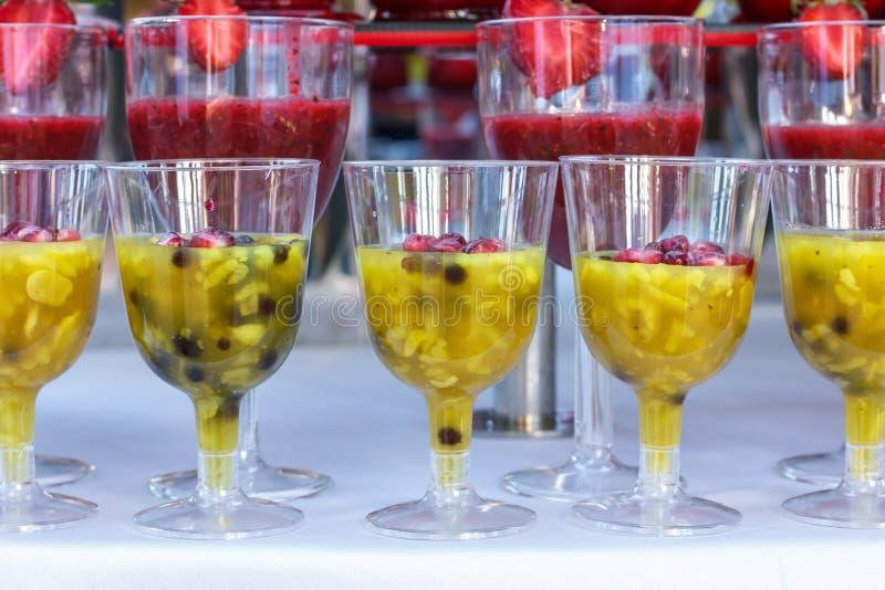 Trituró las frutas frescas - fresas, naranjas y kiwi en tazas fotografía de archivo