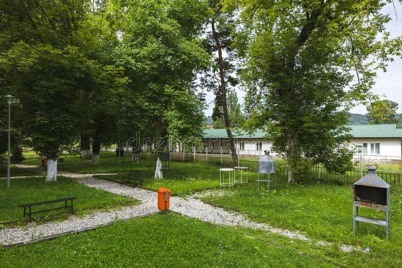 Triumf park, in Campina Romania. Summer morning in the park. Small green park in Campina, Romania, with benches and barbecue places. Summer morning in the park royalty free stock image